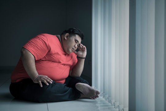 Young obese man looks stressed near the window