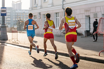 Wall Mural - back group man runners running marathon on street in soft sunlight