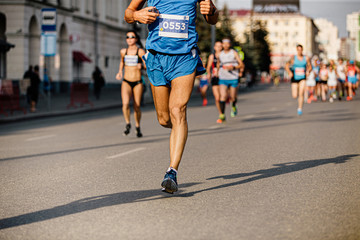Fototapete - male runner run first large group of marathon athletes