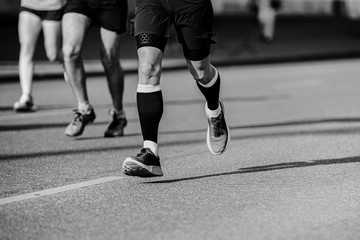 Wall Mural - legs athlete runner in compression socks running street black and white photo