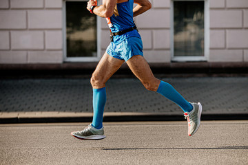 Fototapete - athlete runner in blue compression socks run in street city marathon