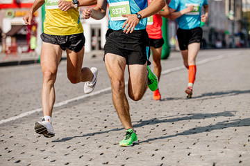 Fototapete - group of runners athletes run on cobblestones city marathon