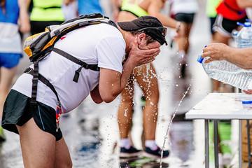 Wall Mural - man runner drinking water at marathon water point