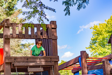 A little boy, about 2 years old, looks down from the high platform on a wooden play structure.
