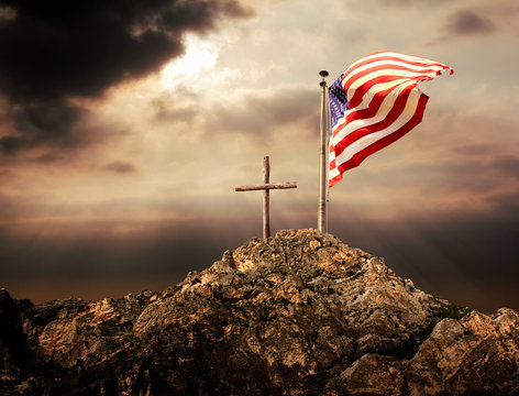 Conceptual image of waving American flag at tall pole and wooden cross over sunset sky