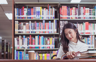 Pretty Asian female student study textbook in library with bookshelf as background in university or college. Concept of education, examination preparation, reading, learning and knowledge searching