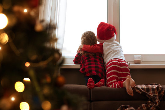 children look out of the window on Christmas