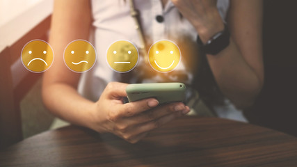 Customer Experience Concept, happy Business women holding the smartphone with a checked box on Excellent Face and Rating for a satisfaction survey. Wall mural