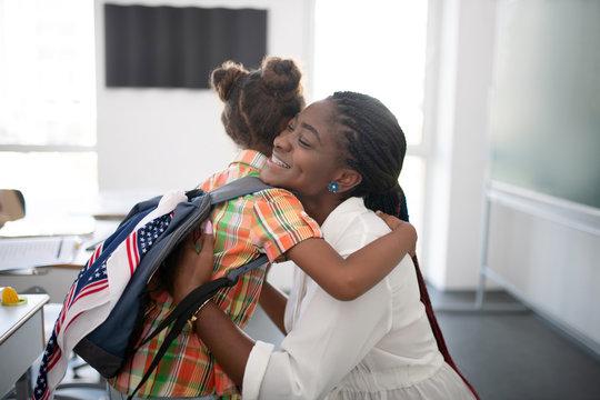 Girl hugging her pleasant teacher while feeling thankful