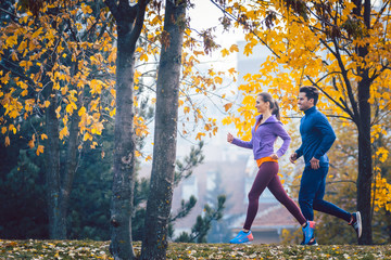 Woman and man jogging or running in park during autumn Wall mural