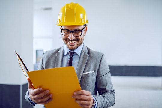 Smiling attractive engineer in a grey suit with a yellow protective helmet on his head holding a yellow folder in his hands and looking at it
