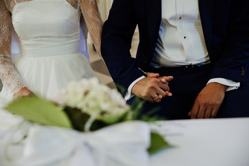the young couple holds hands during the wedding