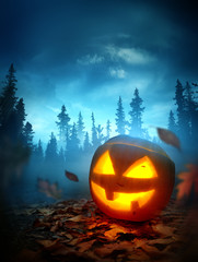 A halloween background with a glowing spooky Jack O Lantern pumpkin outside at night with a forest in the background. Photo composite.