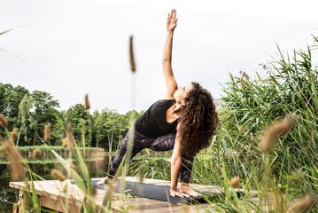 Fototapeta Kobieta ćwiczy jogę na tarasie.  obraz