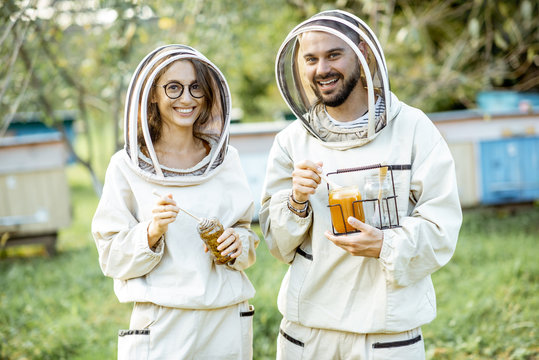 Portrait of a man and woman beekepers in protective uniform standing together with honey in the jar, tasting fresh product on the apiary outdoors