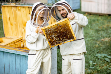 Two young beekepers in protective uniform working on a small apiary farm, getting honeycombs from the wooden beehive