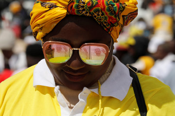 Images of Pope Francis are reflected in the sunglasses of a woman attending a Sunday Mass at the diocesan grounds of Soamandrakizay in Antananarivo