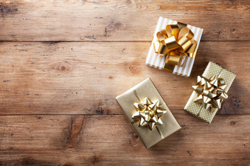 Heap of gift or present boxes on wooden table top view. Festive composition for birthday, christmas or wedding.