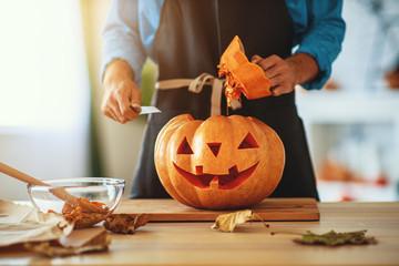 hands of  man cutting pumpkin to halloween.