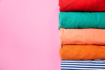 close up of rolled colorful clothes on pink background, preparing for travel