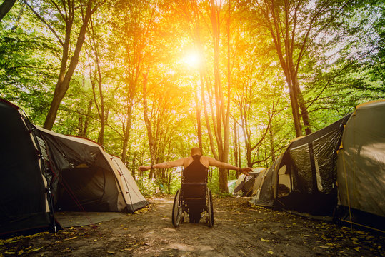 Disabled man resting in a campsite with friends. Wheelchair in the forest on the background of tents
