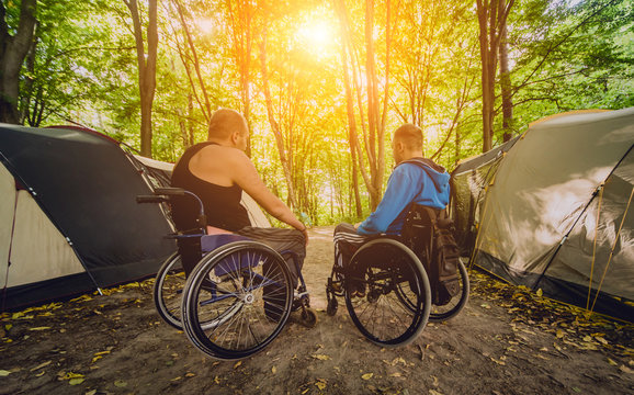 Two disabled men resting in a campsite with friends. Wheelchair in the forest on the background of tents