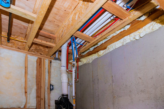New home under construction plumbing PVC pipes inside a home framing with basement view