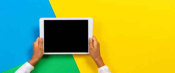 Kid hands with tablet computer on yellow, blue and green background