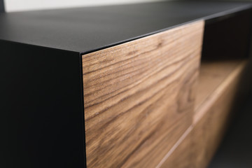 Closeup details of modern tv stand made from walnut and powder coated steed