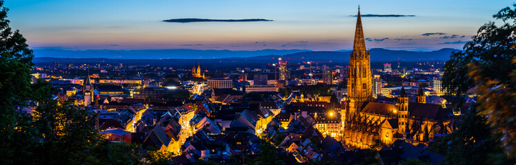 Germany, XXL panorama of city freiburg im breisgau from above in summer in magical twilight atmosphere after sunset Fototapete