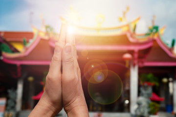 Faith and religious.Woman hands pressing together praying and blessing in front of  chinese shrine with sunlight and bokeh.