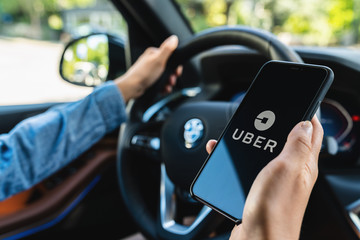 BERLIN, GERMANY JULY 2019: Uber driver holding smartphone in car. Uber is an American company offering transportation services online. Illustrative editorial.