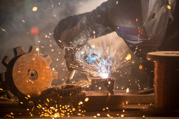 Welder is welding metal part in industrial workshop.