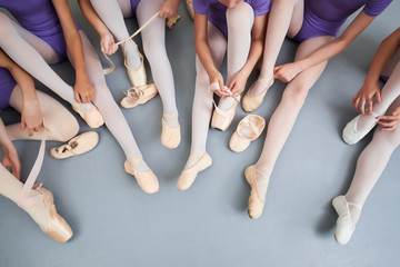 Ballerinas putting on ballet shoes. Group of young ballerinas sitting on the floor and adjusting pointe shoes before dance practice.