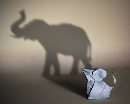 Concept of hidden potential. A paper figure of a mouse  that fills the shadow of  an elephant. 3D illustration