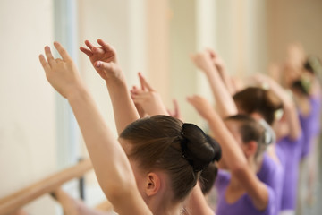 Ballerinas training at class, cropped image. Little ballet girl doing ballet exercises at barre, blurred background. Close up young girl athlete with hair combed into a ball.