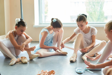 Young ballerinas tying pointe shoes. Four beautiful ballet dancers in dresses sitting on the floor...