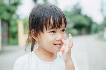 Portrait of little Asian girl pick the nose that is not good behavior in public place.