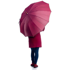 Woman in red coat standing with umbrella looking autumn cold rain on white background isolation, back view