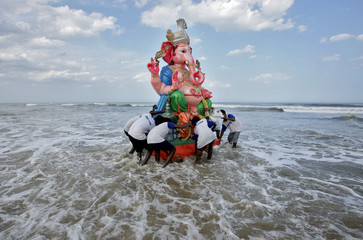 Devotees carry an idol of the Hindu god Ganesh into the Bay of Bengal for its immersion during the ten-day-long Ganesh Chaturthi festival in Chennai