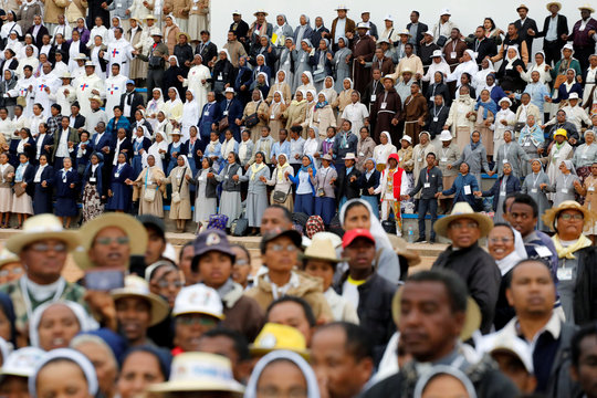 People of the clergy hold hands before the arrival of Pope Francis to the st. Michael College in Antananarivo