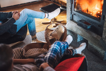 Father with son sitting in comfortable armchairs in their cozy country house near fireplace and enjoying a warm atmosphere and flame moves. Parents and kids time spending concept image.