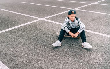 Teenager skateboarder boy with a skateboard sitting on asphalt playground and resting after he made tricks. Youth generation Freetime spending concept image.