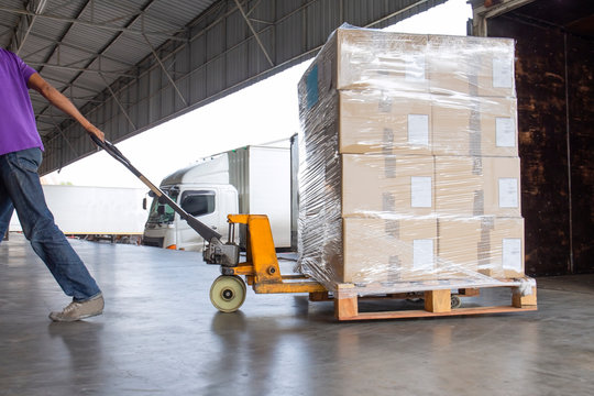 Warehouse cargo logistics and transportation, Worker with hand pallet truck unloading shipment  goods at warehouse dock.