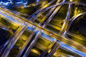 Fotobehang - Aerial view of illuminated road interchange or highway intersection with busy urban traffic speeding on the road at night. Junction network of transportation taken by drone.
