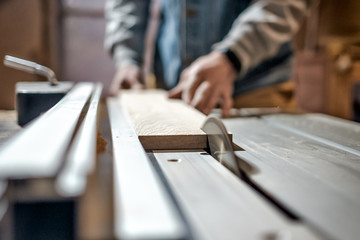 Caucasian man making wooden parts for custom furniture on machine tool called thickness planer in carpentry. Producing lumber concept
