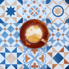 cup of coffee on colorful tile background top view