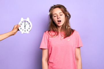 Studio shot of young good looking female in pink pyjamas yawning, trying to wake up, hates early mornings, had bad sleep, disturbing dreams, posing over light purple background.
