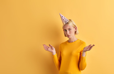 depressed nervous sad beautiful woman shrugging her shoulders, celebrating her birthday. Angry upset teen girl with raised arms, palms doesn't know how to find money to celebrate birthday