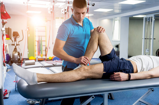 Rehabilitation therapy. Physiotherapist working with young male patient in the rehabilitation center